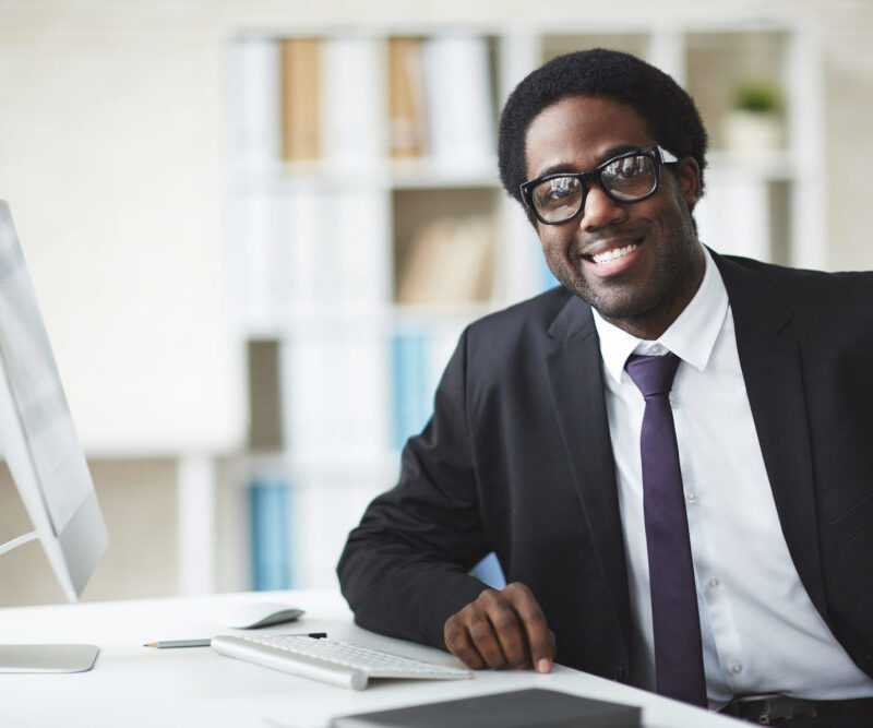Elegant businessman in suit and eyeglasses looking at camera